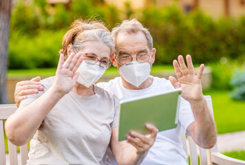 Senior couple wearing protective mask having video chat on tablet computer during the coronavirus...