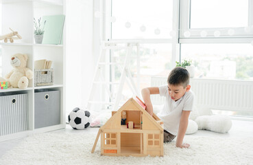 Cute little boy playing alone with wooden house in children's room