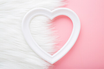 Frame of white heart shape on pastel pink table and fluffy fur blanket. Love and happiness concept. Empty place for cute, emotional, sentimental text, quote or sayings. Closeup. Top view. Two sides.