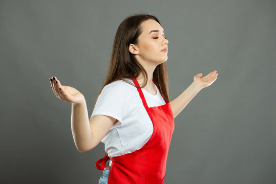 Side view of young female supermarket employee making winner gesture