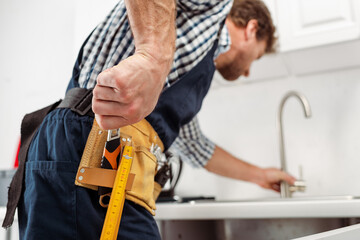 Selective focus of plumber taking wrench from tool belt while fixing faucet in kitchen