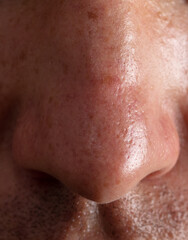 Close-up nose on the face of a man as a background.