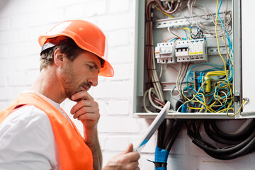 Side view of pensive electrician holding digital tablet near electric panel
