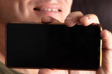 Close up of a black phone screen in a hand.