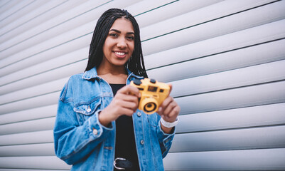 Positive female student holding old fashioned equipment in hands and posing near cope space area...
