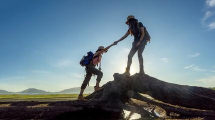 Group Hiker team woman helping her friend climb up timber. Traveler teamwork and family relax...