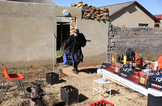 A clergyman of the Gabula church, arrives carrying a crate of empty beer bottles