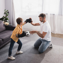 handsome man fighting with cute son in boxing gloves on floor