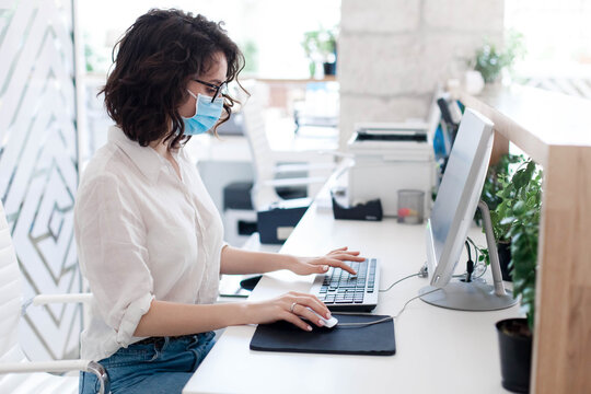 Worker wearing protective mask at hotel reception. Protection employees on safe workplace. Young woman working in office as receptionist. Social distance during coronavirus quarantine, staff safety.