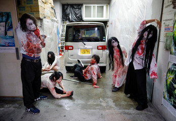 Actors dressed as zombies or ghouls stretch before their performance at a drive-in haunted house show, performed by Kowagarasetai, for people inside a car in order to maintain social distancing amid the spread of the coronavirus disease (COVID-19), in Tok