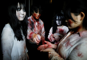 Actors dressed as zombies or ghouls disinfect their hands before their performance at a drive-in haunted house show by Kowagarasetai, for people inside a car in order to maintain social distancing amid the spread of the coronavirus disease (COVI