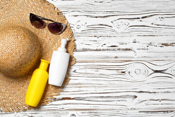 Straw hat, sunglasses and sunscreen bottle on wooden background