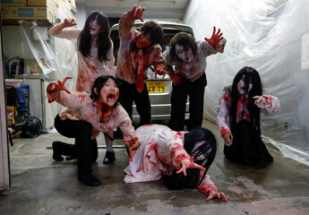 Actors dressed as zombies or ghouls pose for a photograph before their performance at a drive-in haunted house show by Kowagarasetai, in Tokyo