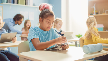 Elementary School Computer Science Class: Cute Girl Uses Digital Tablet Computer, Her Classmates...