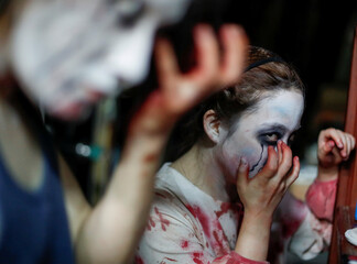 Actors dressed as zombies or ghouls put makeup on before a drive-in haunted house show, perfromed by Kowagarasetai, in Tokyo