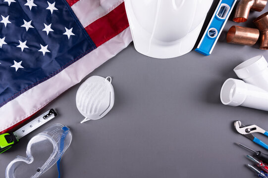 Happy Labor day,  Construction tools, face mask  and USA flag on grey background. Labor day  concept.  Copy space.