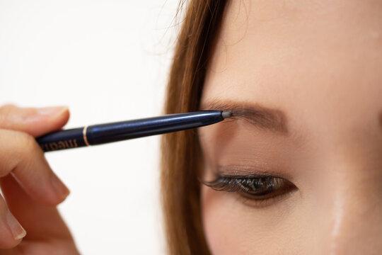 アイブロウペンシルで眉毛を描く女性