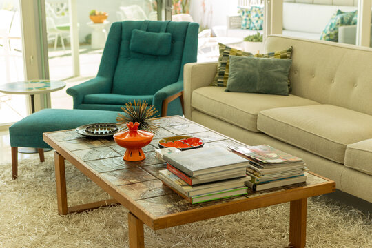 Sunny mid-century modern 1950s home living room interior in Palm Springs California with coffee table, books, sofa