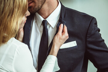 Young businesswoman holding jacket collar of businessman. Flirting couple of unrecognizable caucasian people. Passionate love affair in office workplace. Close up shot.