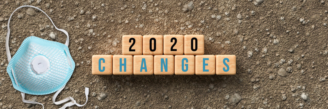 cubes with message 2020 CHANGES and a face mask on dirt gravel background