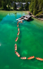 Aerial view of the Lake Braies, Pragser Wildsee is a lake in the Prags Dolomites in South Tyrol, Italy. View of rowboats moored in line. In the background the hotel surrounded by trees