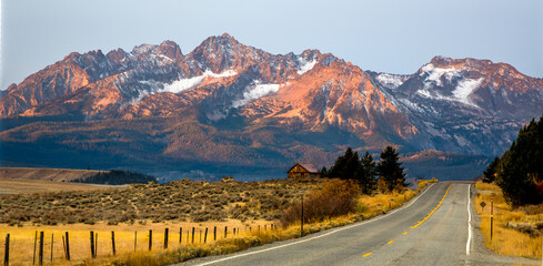 The Sawtooth mountains and a log cabin at sunrise and highway 75 leading to Stanley, Idaho.