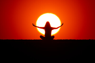 Wall Murals Red Young girl doing yoga exercises at sunset. In the background the big sun can be seen behind the silhouette of the girl. The concept of nature and beauty. Orange sunset.