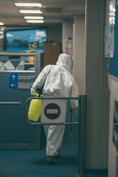 Disinfection in the office building. Human in HAZMAT white suit