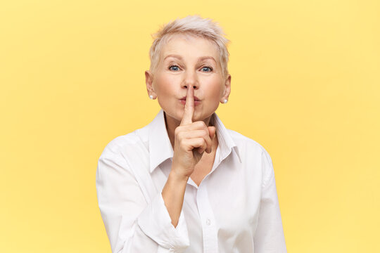 Portrait of stylish attractive middle aged businesswoman in white shirt holding fore finger on her lips, asking you to keep silent about commercial secret, making shh gesture. Mature female shushing