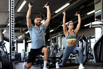 Attractive sports people are working out with dumbbells at gym.
