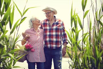 Loving senior man and woman goes on the pond at picnic.  Senior people at picnic.