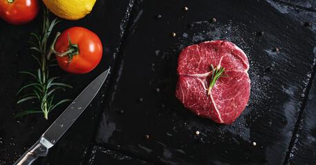 Raw meat steak Tenderloin fillet, with vegetables on black stone plate