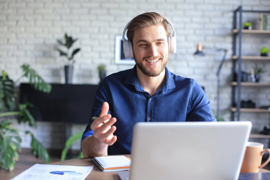 Confident man wearing headset speaking and watching business webinar training, listening to lecture.