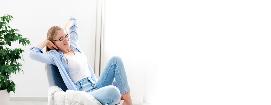 Young woman relaxing under air conditioner at home. Girl resting on couch, enjoying cool fresh air in cozy living room. White background, copy space. Self isolation, social distance in quarantine.