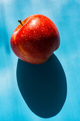 Red apple and shadow lies on a blue background.