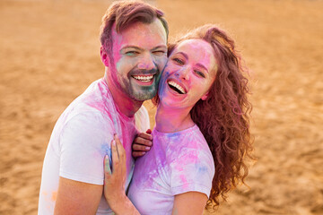 Excited couple having fun during paint festival
