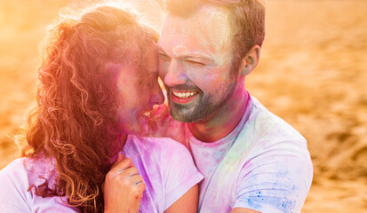 Optimistic couple with colorful faces on beach