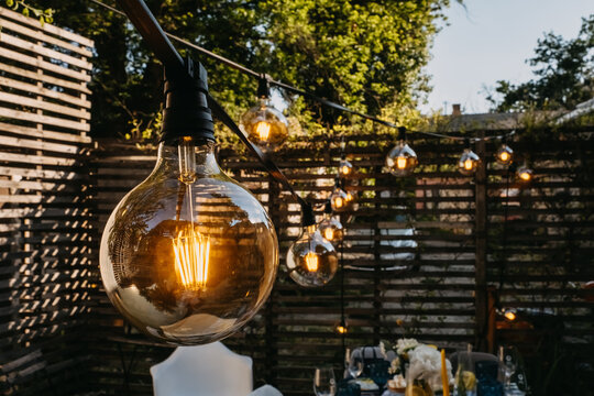 Light bulbs outdoors at a party in evening time.