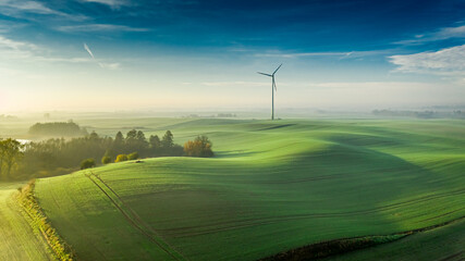 Foggy green field and wind turbine at sunrise, Poland