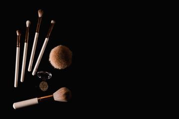 Elegantly lit make-up brushes on a black background