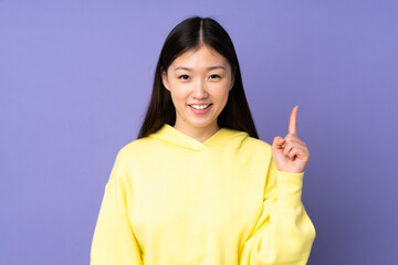 Young asian woman isolated on purple background showing and lifting a finger in sign of the best