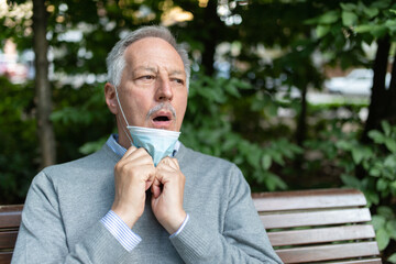 Man having difficulty to breath with his mask on, coronavirus prevention in summer concept