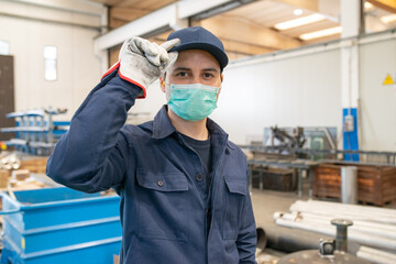 Worker in a factory wearing a mask and holding his protective hat
