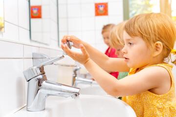 Obraz Child in kindergarten washing her hands - fototapety do salonu