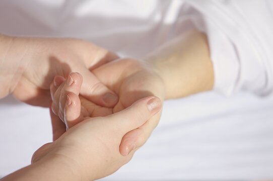 Hand treatment of two people in white