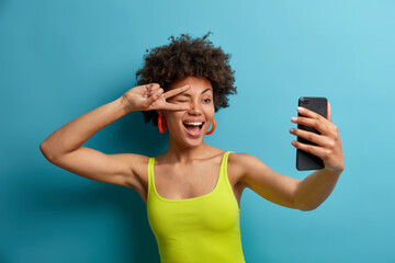 Playful positive curly haired woman makes peace sign over eye, takes selfie on smartphone, shows...