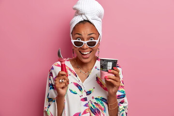 People, summer mood and nutrition concept. Happy stylish woman eats cold ice cream, holds spoon, smiles pleasantly, wears sunglasses, dressed in domestic clothes with jewelry, enjoys pleasant taste