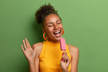 Positive African American woman chills with cold strawberry ice cream, sings and has fun during hot...