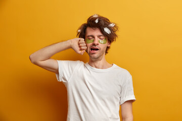 Photo of young man with messy uncombed hair, collagen pads under eyes, yawns early in morning,...