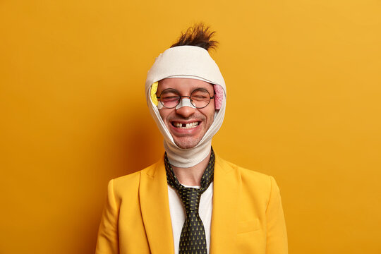 Health care and injury concept. Happy positive young man smiles broadly and shows missing teeth, recovers after being beaten, wears bandage on head and formal suit, has funny face expression